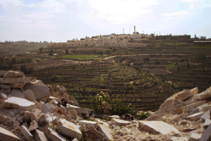 Israeli-Settlement-Daoud-Over-Pile-of-Stones